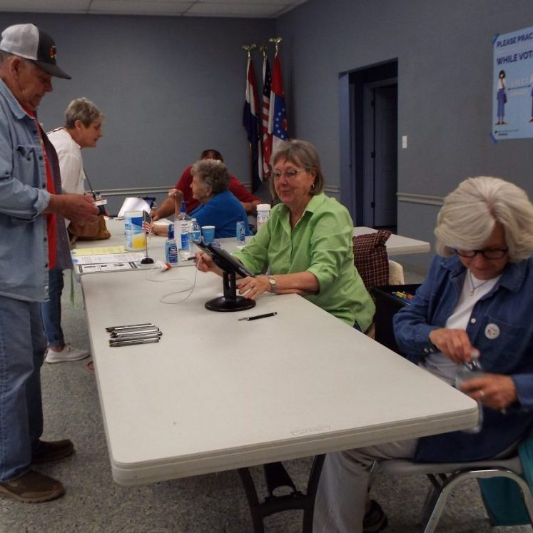 """Photo by Christy Porter Helping voters on Tuesday were, seated from left: Election judges Danny Howell and Margaret Burch, and Supervisory judges Brenda Bartleson and Donna Reed. Richard Hofstetter was receiving his ballot. Deputy County Clerk Linda Roberts was supervising the ballot box and giving voters an """"I Voted"""" sticker."""